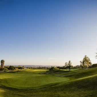 Golf course in Fallbrook California at sunset. Scenic view of the bright green fairway of a golf course in Fallbrook, California. The setting sun shines brightly in the vast horizon.